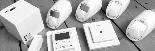 Ausgepackte Komponenten der MAX! Heizungssteuerung: MAX! Cube, 4 MAX! Heizkörperthermostate Basic, MAX! Eco Taster, MAX! Wandthermostat und ein MAX! Fensterkontakt sind zu sehen.